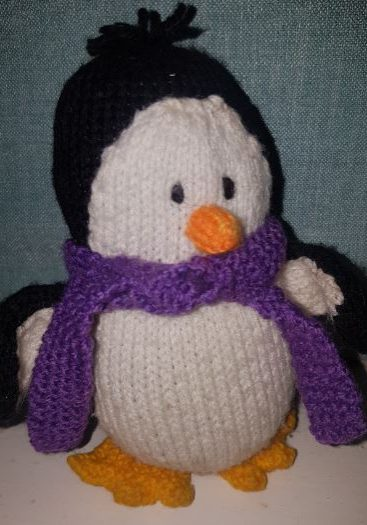 Handmade children fitting in knitting penguin creation